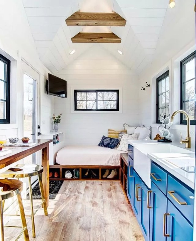 Tiny home with bright blue cabinets and bed with storage. Photo by Instagram user @atinyhouse_nh