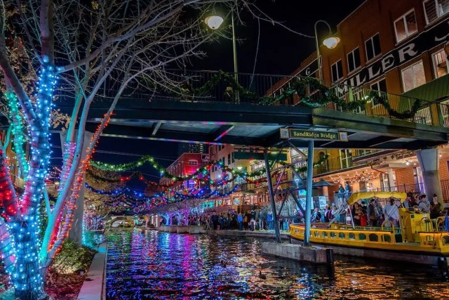 Water taxi driving by trees with colorful lights. Photo by Instagram user @bricktownwatertaxi