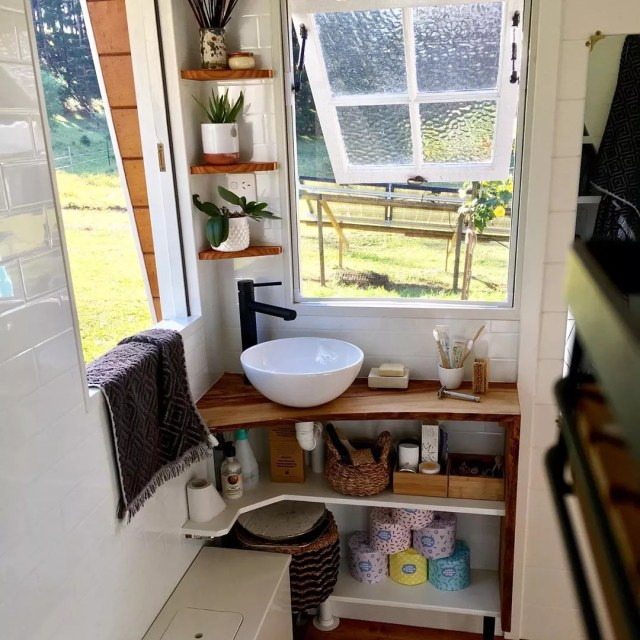 Tiny bathroom with windows open and shelves in the corner. Photo by Instagram user @little_things_tinyhouse