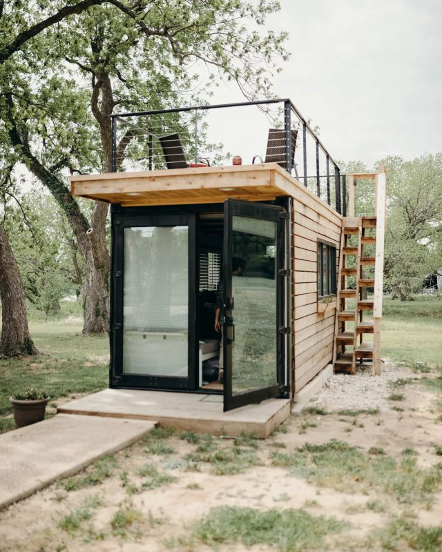 Small wooden tiny home with black doors. Photo by Instagram user @alexis_mccurdy