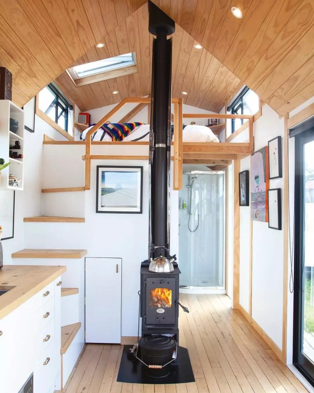Tiny home with wood floors and white walls and black wood stove. Photo by Instagram user @camandas_tinyhouse