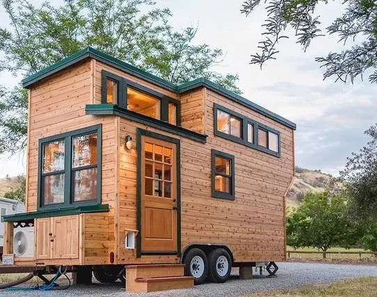 All wood tiny home with green trim on wheels. Photo by Instagram user @californiatinyhouse