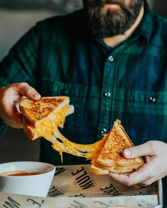 Guy pulling apart cheesy grilled cheese. Photo by Instagram user @dwellingtable