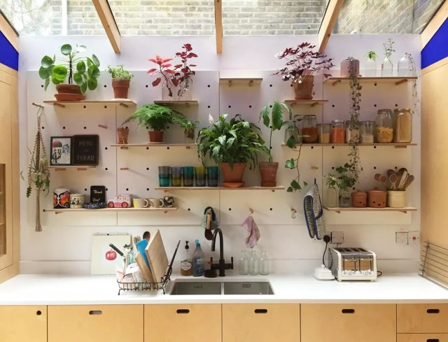 Pegboard wall full of plants and decor. Photo by Instagram user @kreisdesign