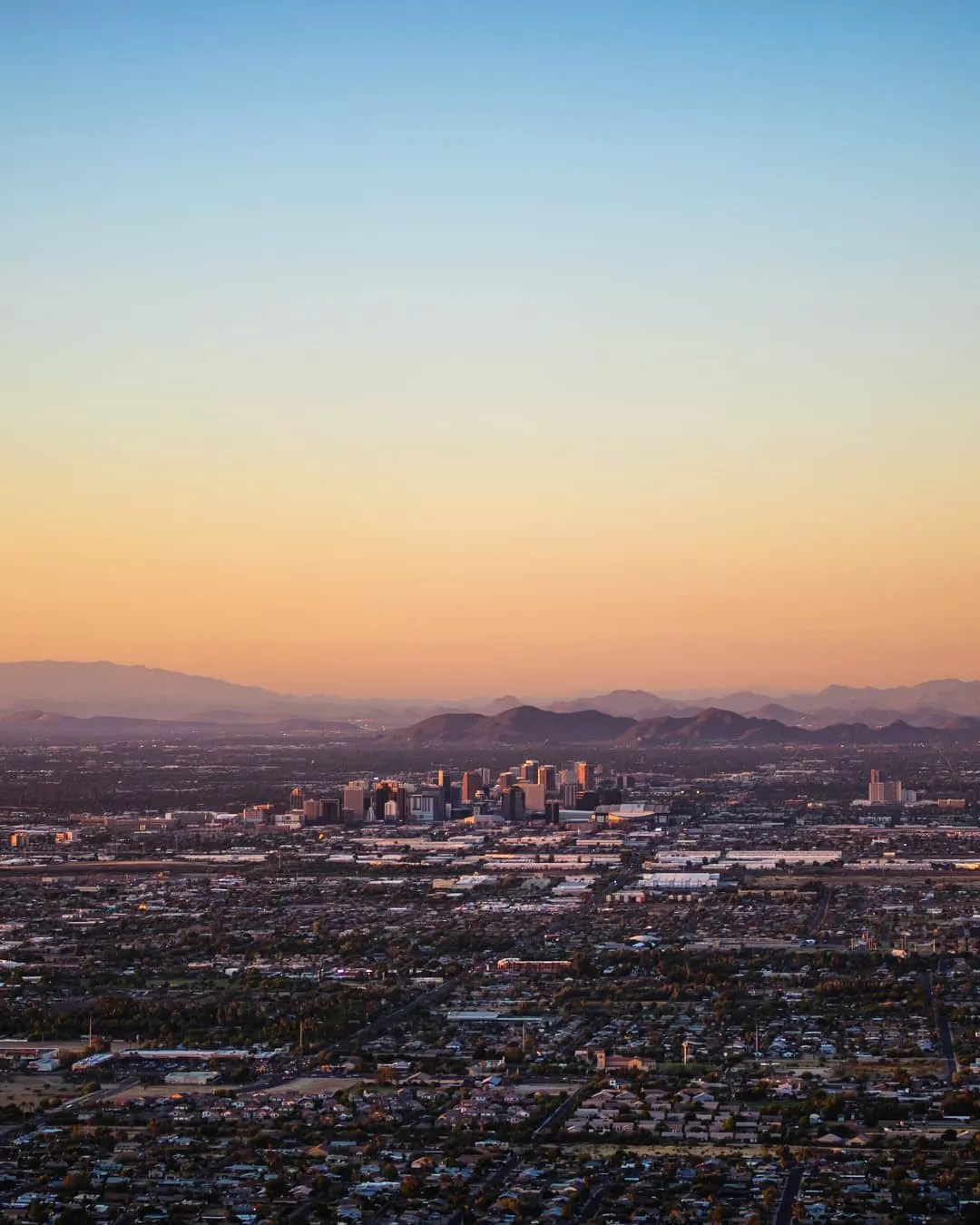 Skyline of mountains and buildings in Phoenix, AZ. Photo by Instagram user @maverick_shots