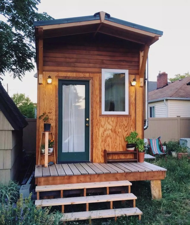 Green front door on all wood tiny home. Photo by Instagram user @nicole_mark