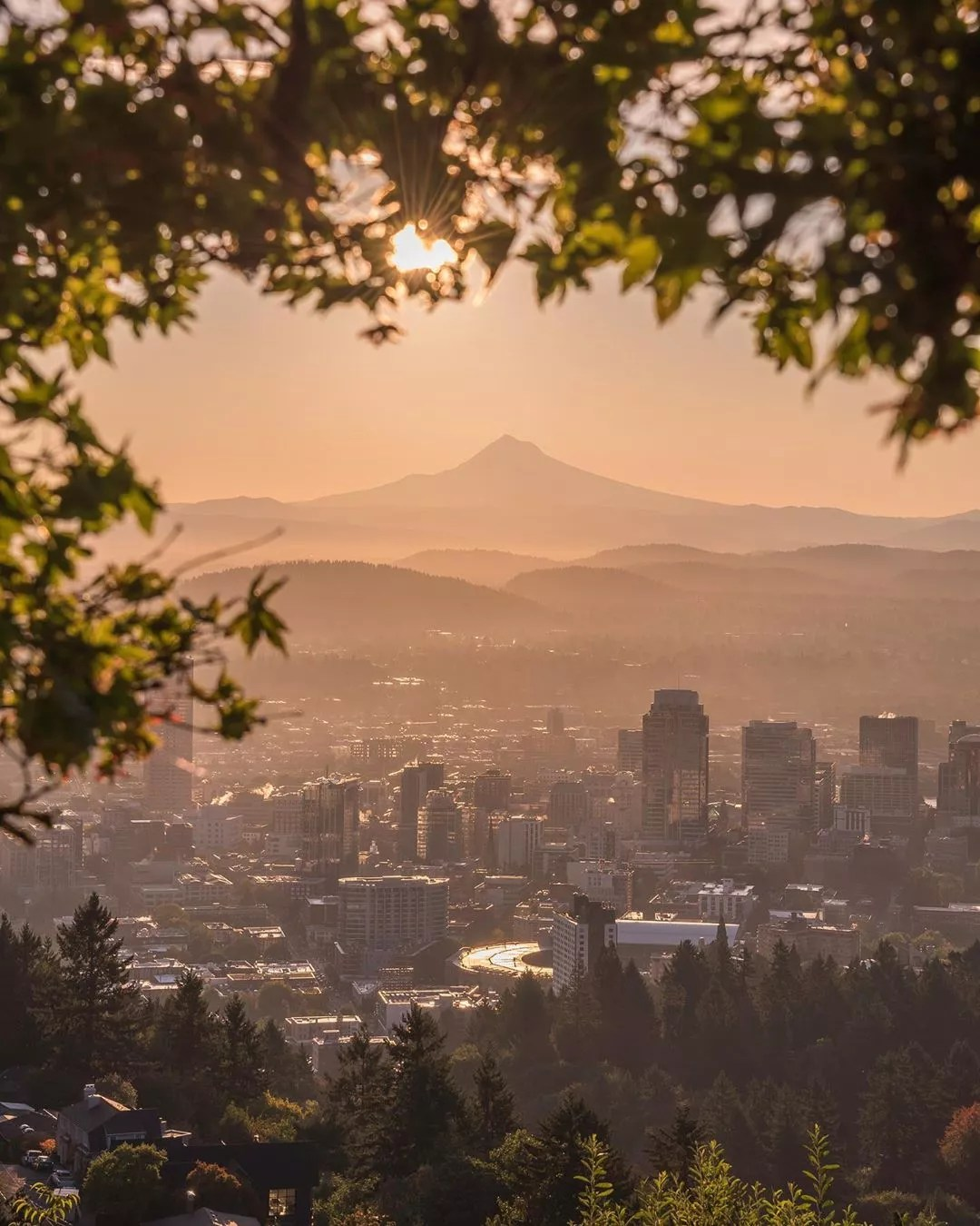 Skyline of tall buildings and mountains during sun rise in Portland, OR. Photo by Instagram user @50shadesofpnw