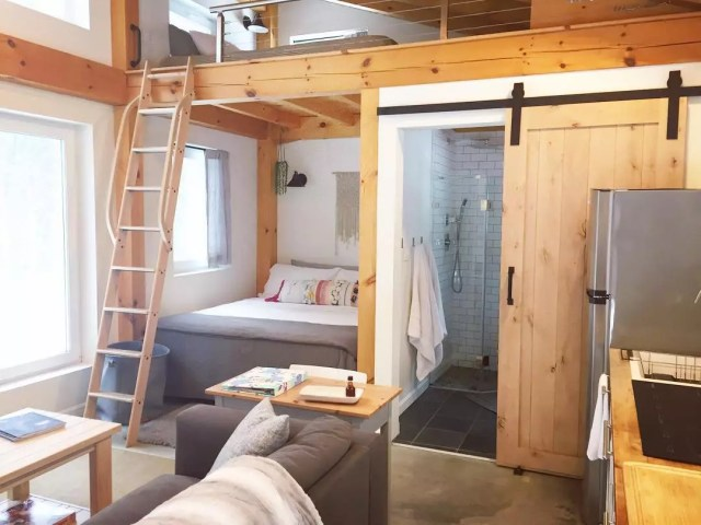 Tiny home bed and bathroom with wood walls. Photo by Instagram user @honeycrisp_cottage