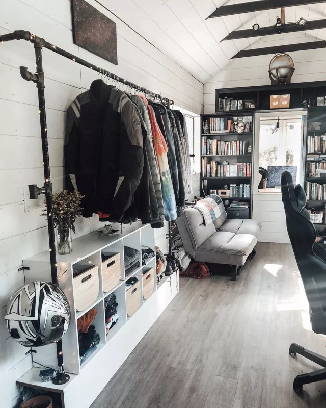 Tiny home with white walls and clothes hanging from a rod. Photo by Instagram user @nicolettenotes