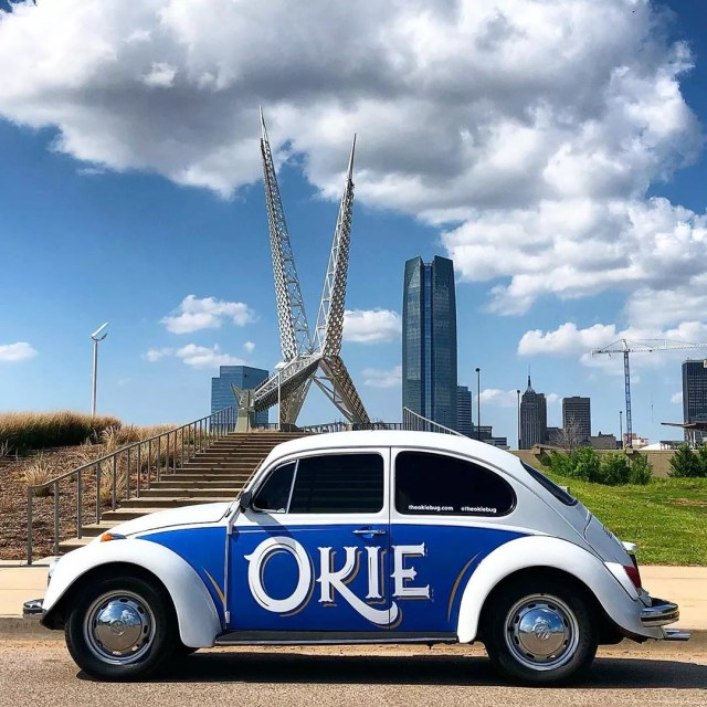 White and blue car parked outside in front of sculpture. Photo by Instagram user @theokiebug