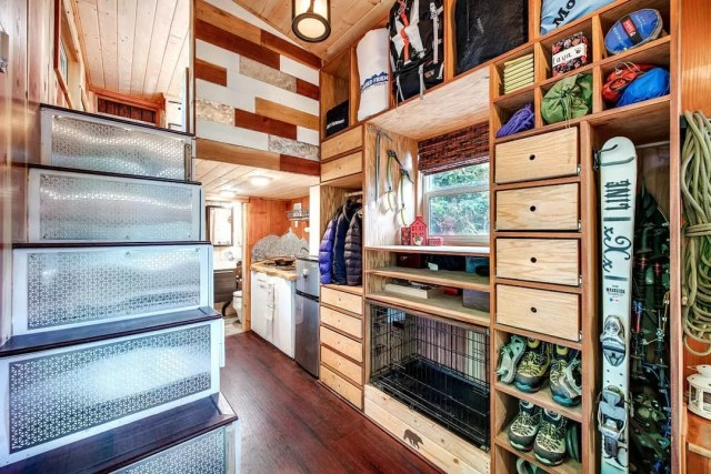 Storage wall in tiny home filled with snow gear. Photo by Instagram user @backcountrytinyhomes