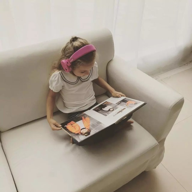 Girl reading book on white chair. Photo by Instagram user @rockpapafan