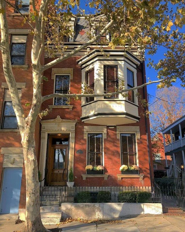 Red brick rowhouse with tree in front. Photo by Instagram user @overtherhine