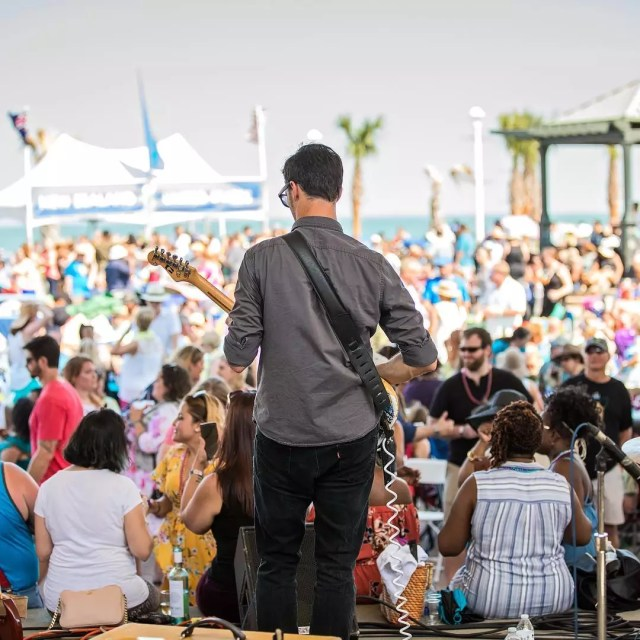 Guy standing on stage playing guitar at festival. Photo by Instagram user @neptunefestival