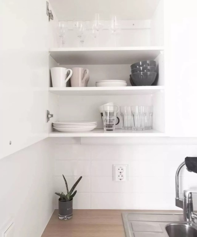 White kitchen with cabinet fulled or gray and white dishes. Photo by Instagram user @minimalismista