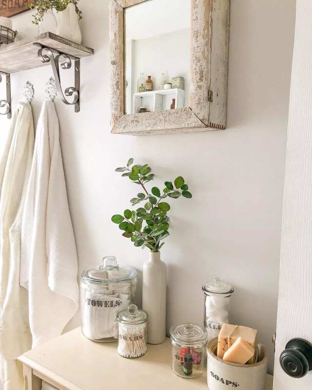 White cabinet with glass jars and rustic mirror hung above cabinet. Photo by Instagram user @the.huber.homestead