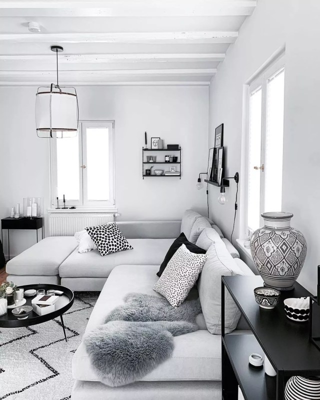 Light gray living room with gray couch and black decor. Photo by Instagram user @froehlicheszuhause