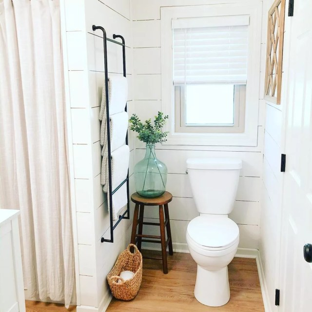 White bathroom with wood floors and vase on stool by toilet. Photo by Instagram user @tinycottageonpetes
