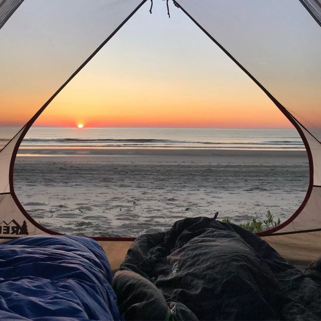 Tent sitting on beach facing the ocean at sunset. Photo by Instagram user @our.weekend.adventures
