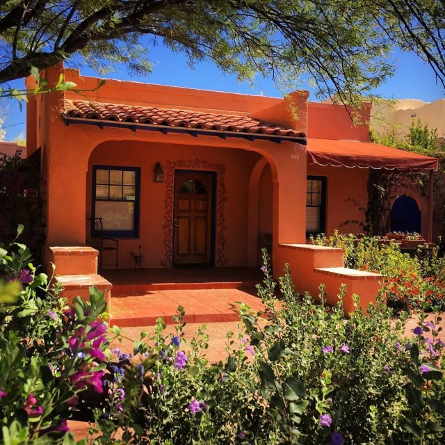 Orange house with red tole roof and plants in front yard. Photo by Instagram user @fotosimmons