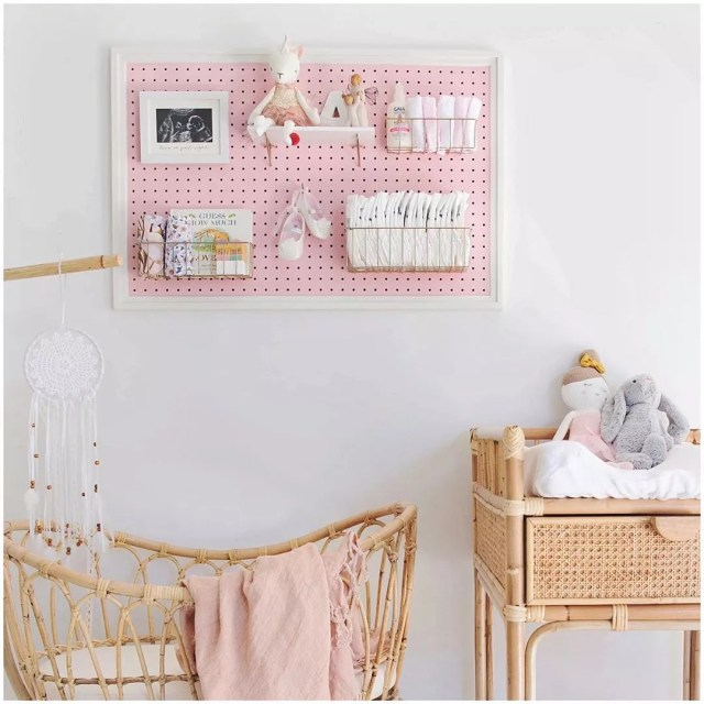 pink homemade pegboard with items stuck to it and wooden bassinet photo by Instagram user @pinpegandhome