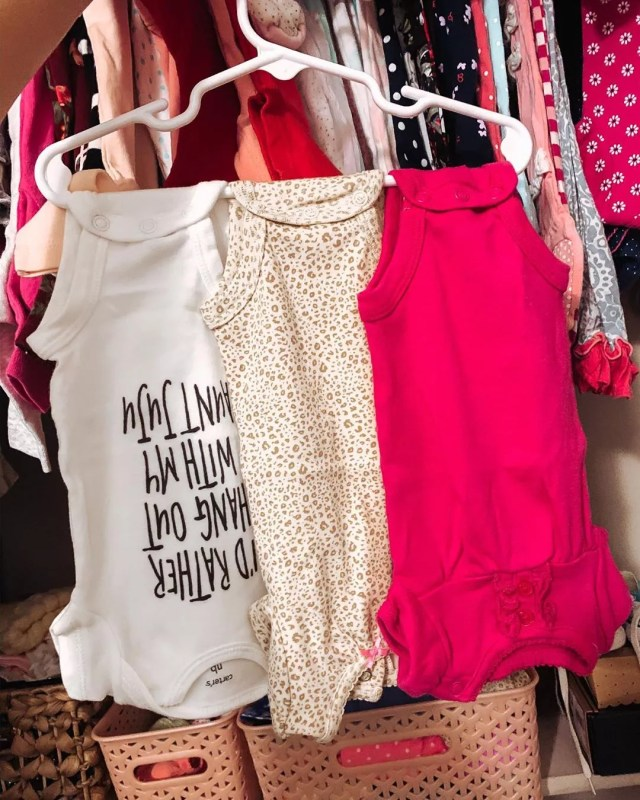 hanger with multiple baby clothes hanging off of it photo by Instagram user @joelle_mcclune