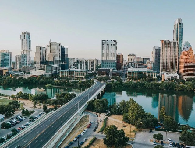 austin skyline with the colorado river in the foreground photo by Instagram user @ammietheexplorer