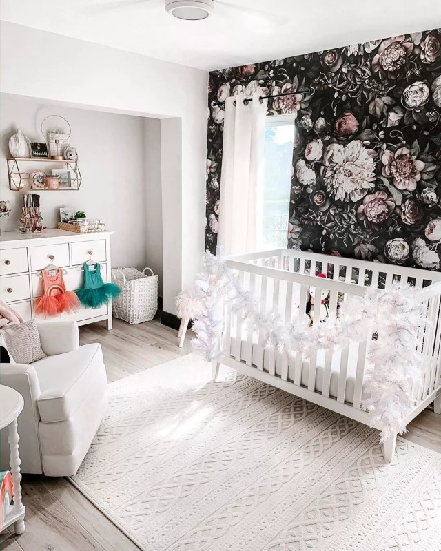 White nursery with black floral wall. Photo by Instagram user @the_floridagirl