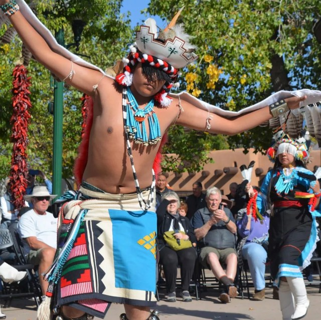 man dancing in traditional native american dress photo by Instagram user @cityofsantafe