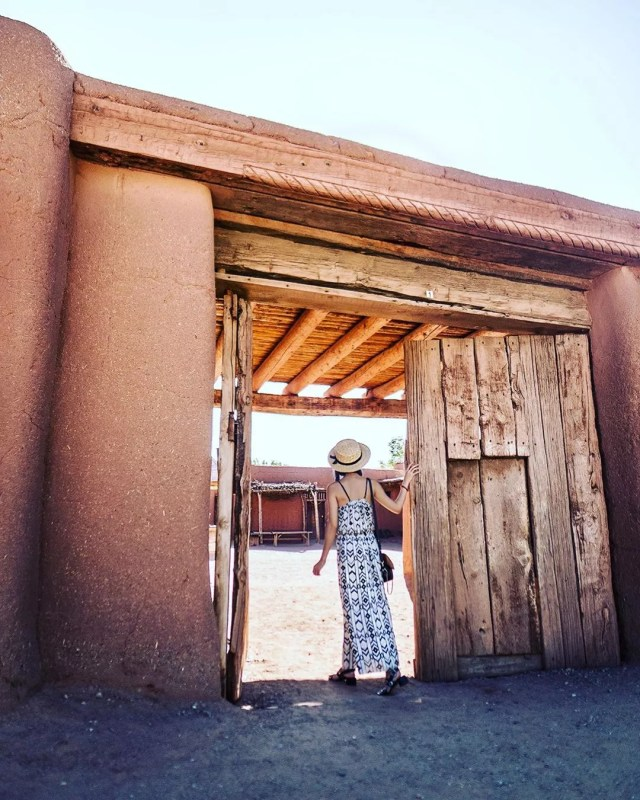 woman standing in the doorway at el rancho de las golondrinas photo by Instagram user @cityofsantafe