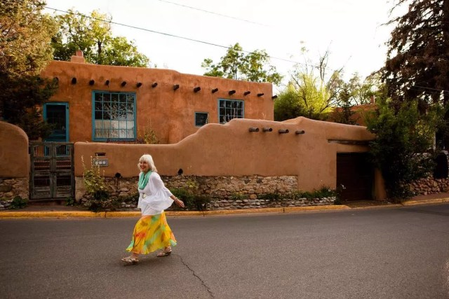 old woman with gray hair walking in the street in santa fe photo by Instagram user @cityofsantafe