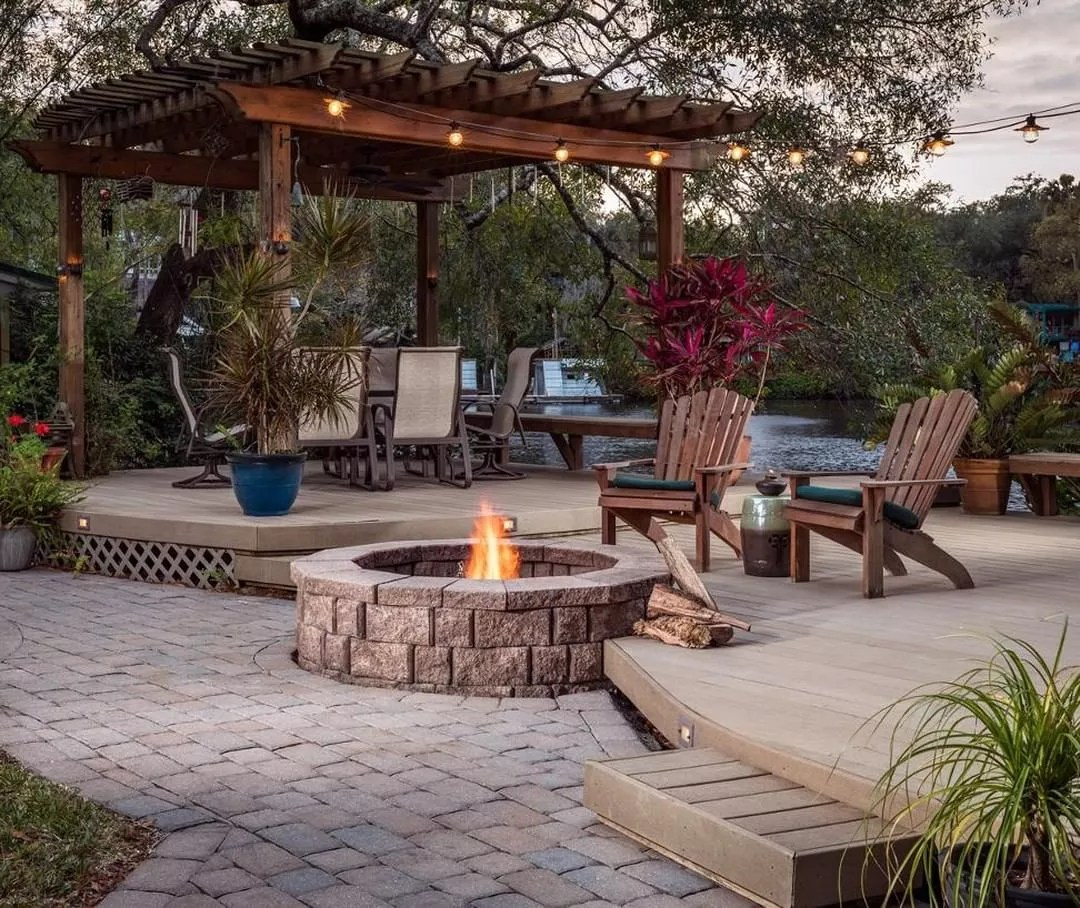 backyard patio area with firepit and pergola with seating all around photo by Instagram user @jjmaterials