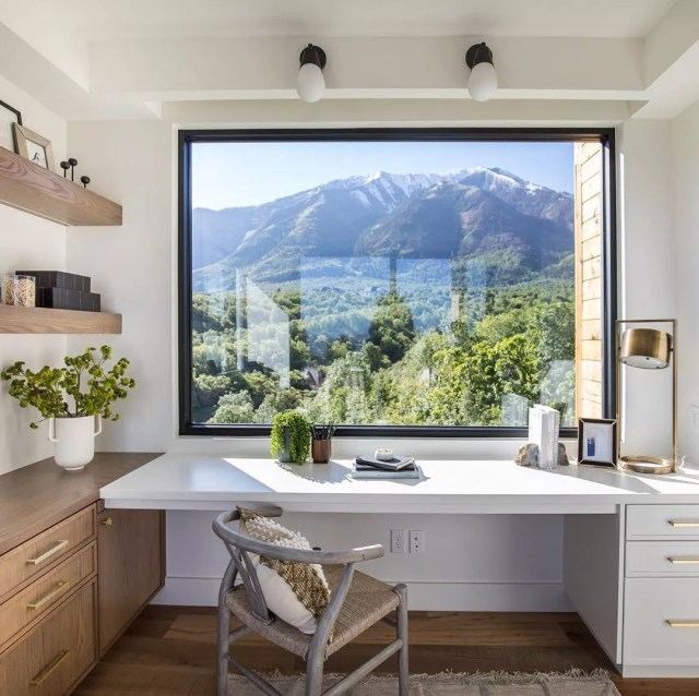 home office space with white floating desk with large window photo by Instagram user @splitrockcustomhomes