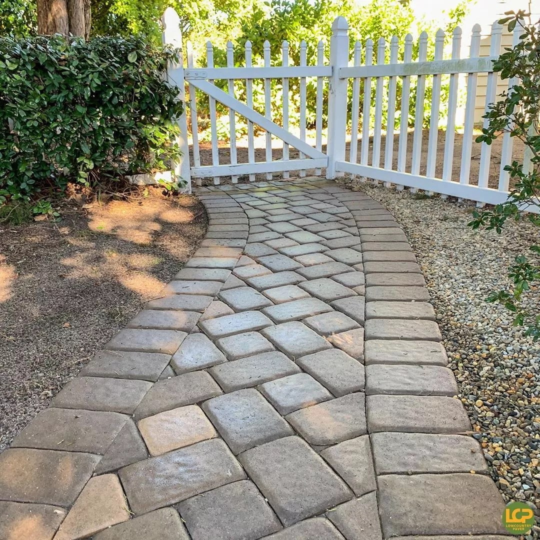 walkway with paving stones laid down with white fence photo by Instagram user @lowcountry_paver