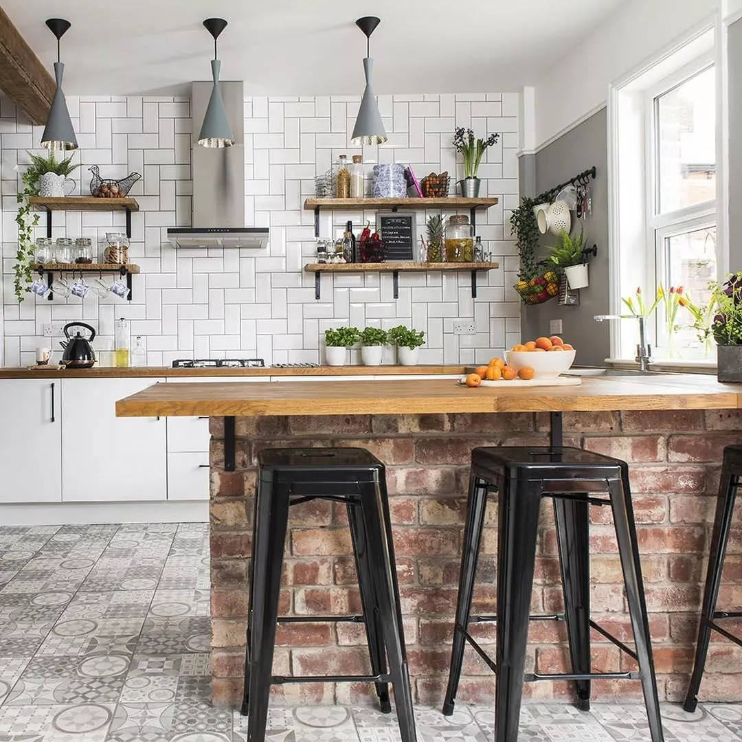 kitchen area with nice breakfast bar with metal bar stools photo by Instagram user @styleathomemag