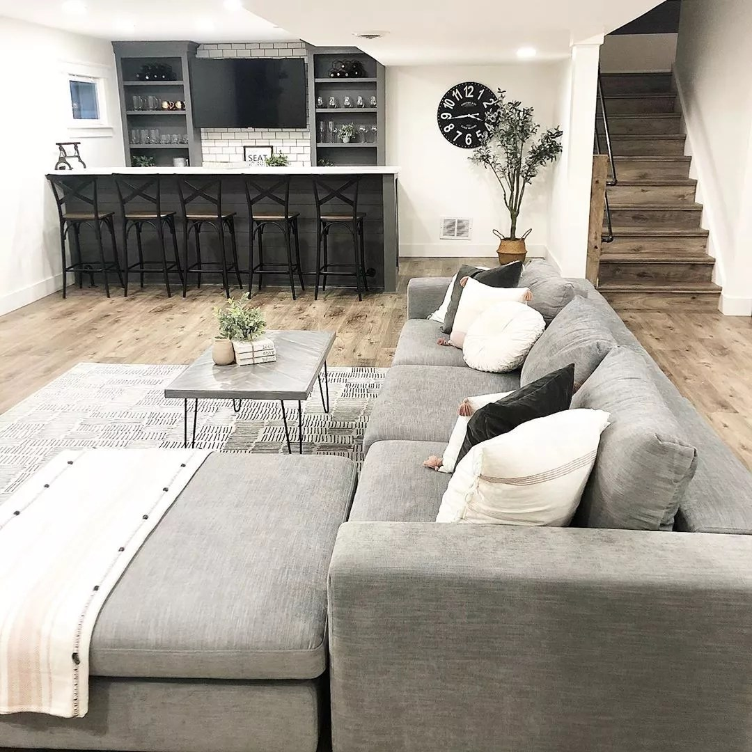 finished basement with full bar and large sectional photo by Instagram user @briemarie1023