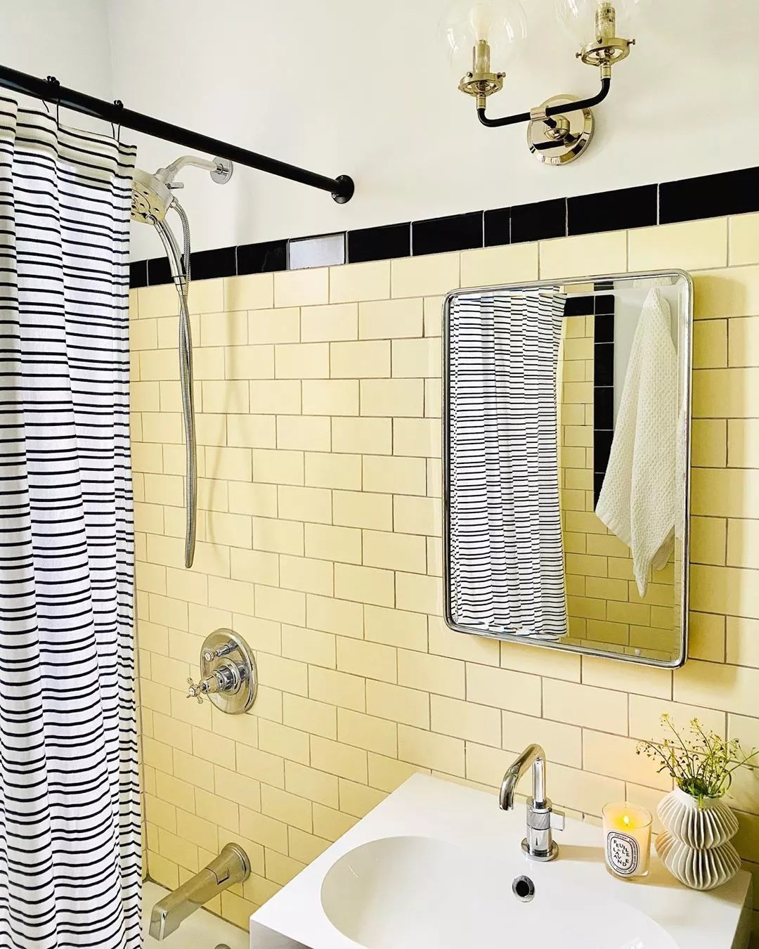updated bathroom walls with yellow subway tiles and new light fixture photo by Instagram user @ipatrickdesign