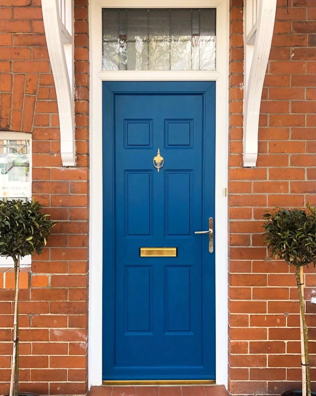 blue front door with plants on both sides photo by Instagram user @renovating_the_broadway