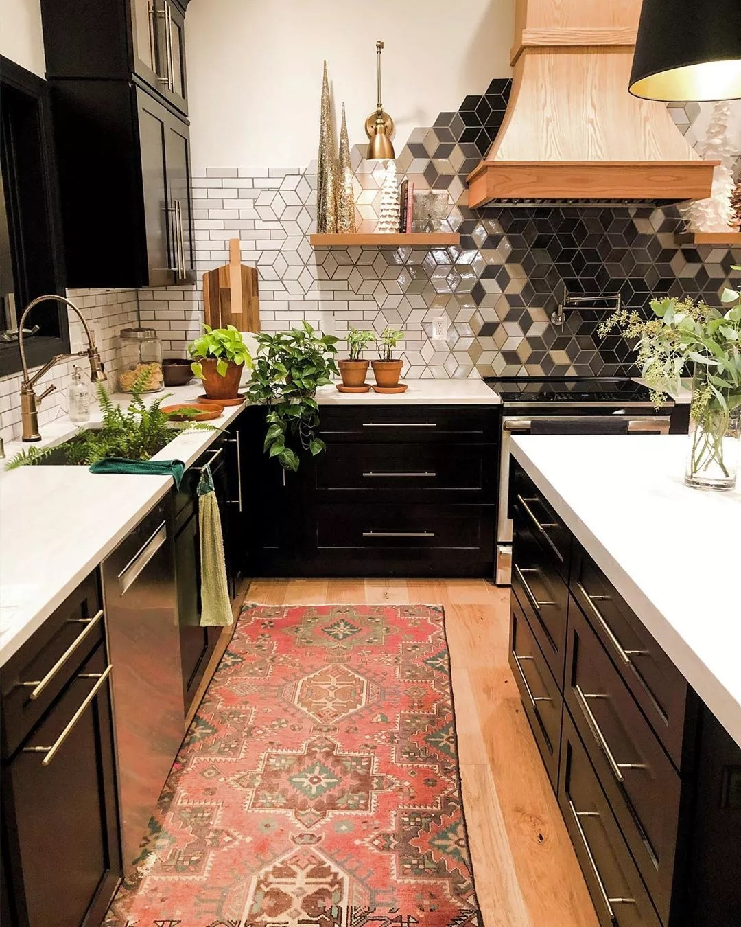 updated kitchen with black cabinets and custom backsplash photo by Instagram user @construction2style