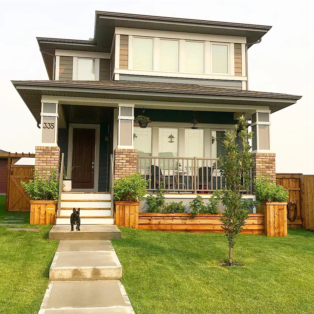 two story home with small tree planted and DIY wooden planters at the front of the house photo by Instagram user @bfulk.handmade