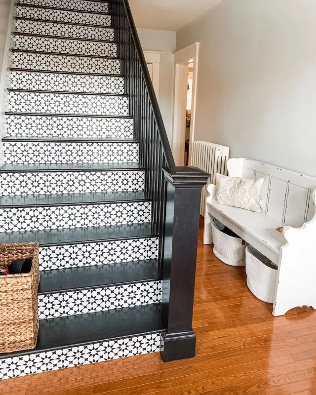 home staircase with black balusters and knule post and wallpaper installed on stairs photo by Instagram user @chasingquinndesign