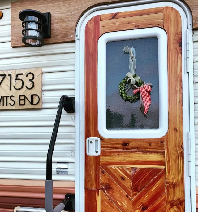 updated exterior of an RV with reclaimed wood on door and new porch light photo by Instagram user @robyns__nest__