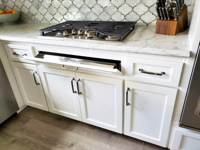 Countertop stove with tip out tray in front. Photo by Instagram user @jlcustomfinishes