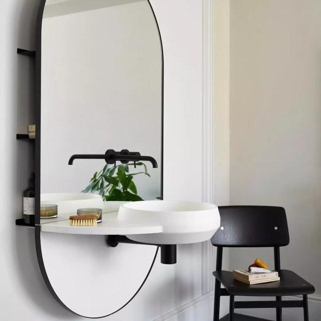 Small shelves hidden behind modern mirror attached to bathroom sink. Photo by Instagram user @westonebathrooms