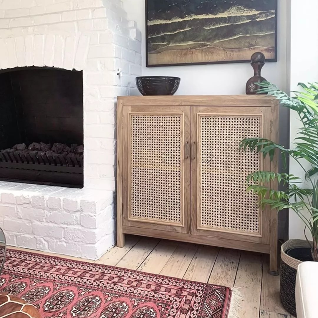 Rattan Cabinet Placed Between Wall and Fireplace for Added Storage. Photo by Instagram user @corcovadostore