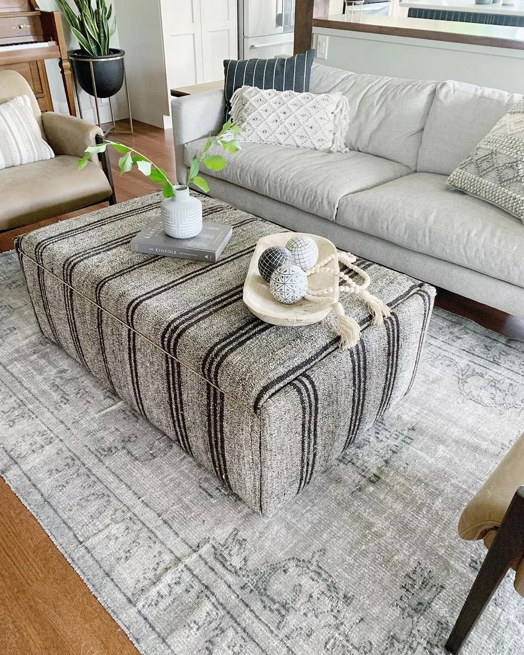 Storage Ottoman placed in the middle of a living room. Photo by Instagram user @courtneyungaro_spaceanddesign