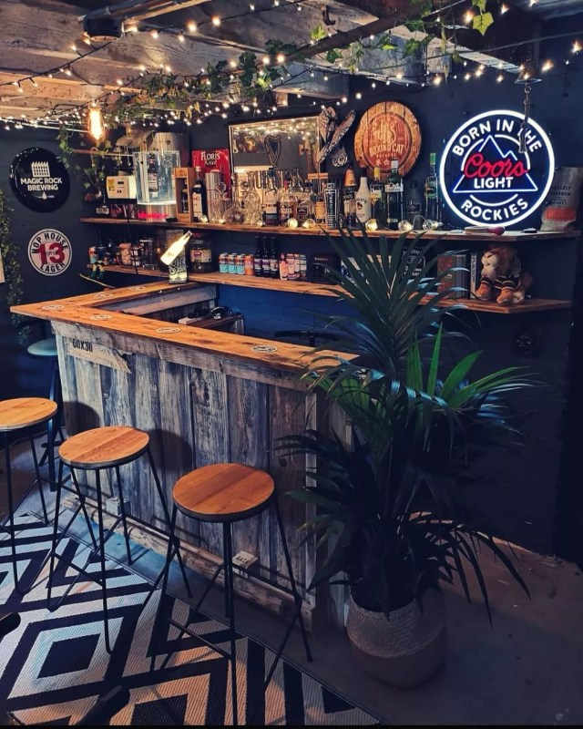 Classic Home Bar Setup with Drinks on the Wall and Light Up Coors Light Sign. Photo by Instagram user @one_two_miss_a_few