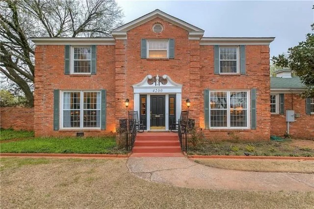 Classic Brick Colonial Home with Greenish Blue Shutters in Forest Park, Oklahoma. Photo by Instagram user @verbodegroup