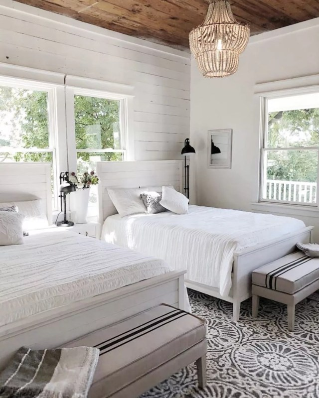 Farmhouse Style Bedroom with Barnwood Wall and White Linens on Two Queen Beds. Photo by Instagram user @my100yearoldhome