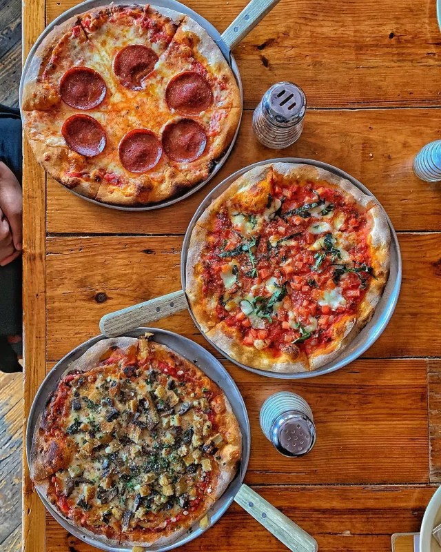 Three Different Types of Pizza on a Table at Sticks and Stones Clay Oven Pizza. Photo by Instagram user @plazoo_bbq
